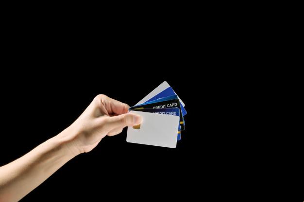 Mano sostiene demasiadas tarjetas de crédito