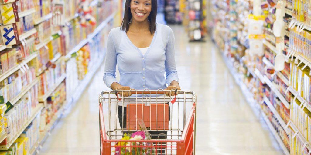 mujer en el super comprando con tarjetas