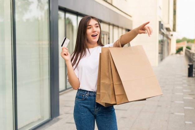 mujer feliz comprando con sus tarjetas